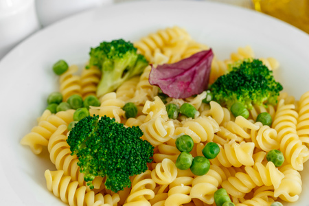 Pasta with broccoli and green peas in a plate close-up