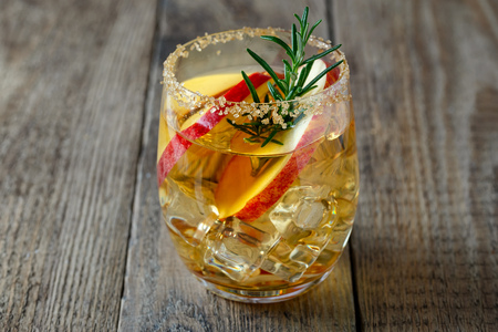 Apple drink with apple slices in a glass, a sprig of rosemary and brown sugar on the rim of a glass