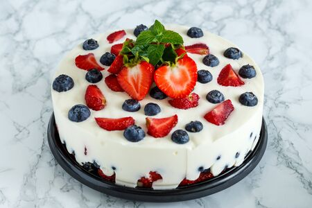 Berry dessert with blueberries and strawberries on the basis of yogurt on a metal dish