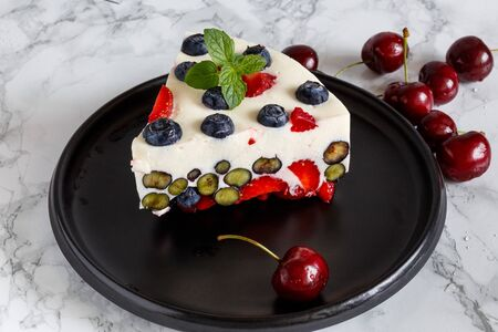 Berry dessert with blueberries and strawberries on the basis of yogurt on a black ceramic dish decorated with berries and mint Standard-Bild