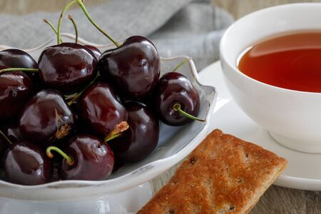 Sweet cherries in a vase with a cup of tea and biscuits, close-up fragment