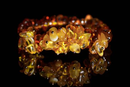 Fragment of a yellow and brown amber bracelet on a black background with reflection Imagens