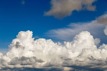 Cumulus clouds of white-gray color against a blue sky after a thunderstorm