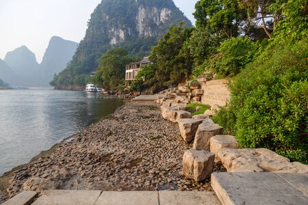 Picturesque riverbank and mountain landscape in the distance, Yangshuo, China, Asia Imagens
