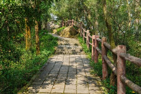 Concrete tile walkway with log railing in a mountain park, Shenzhen, China Imagens