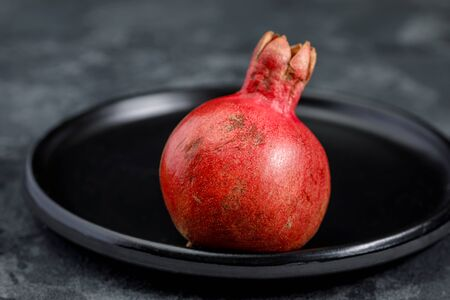 Pomegranate fruit on a red ceramic dish, whole, small, against a dark background