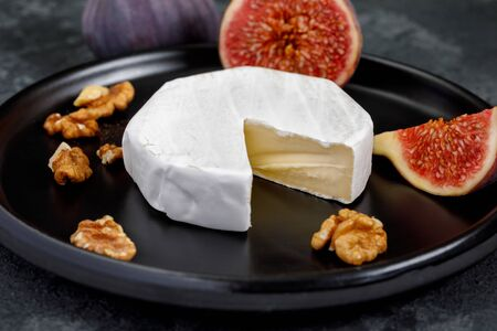 Camembert cheese on a ceramic dish with peeled walnuts and figs Imagens