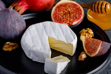 Camembert cheese on a ceramic dish with peeled walnuts and figs, honey and pomegranate Imagens