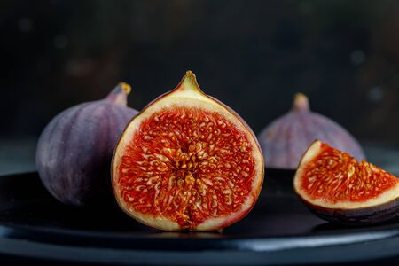 Tropical fig fruit, fresh in half section on the background of whole fruits and quarters
