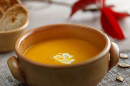 Pumpkin cream soup in a ceramic dish with breadcrumbs and red autumn leaves in the background