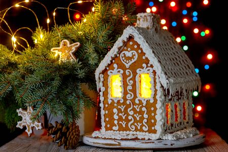 Gingerbread house with bokeh of light bulbs in the background and sprigs of blue spruce
