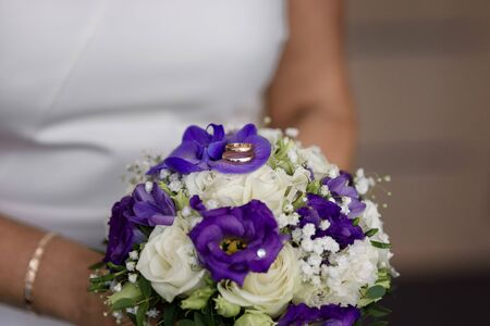 Wedding rings lying on the brides bouquet of white and purple flowers in the hands of the bride Stock Photo