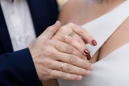 Wedding rings on the hands of the bride and groom close-up