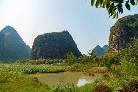 Field with lotuses and a pond in the mountain valley of Yangshuo, Guilin, China