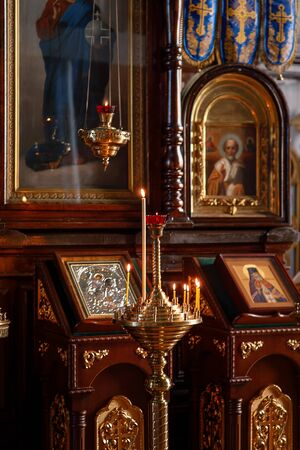Decoration of the Orthodox Church, Church candlestick with burning candles, icons in the background in the background