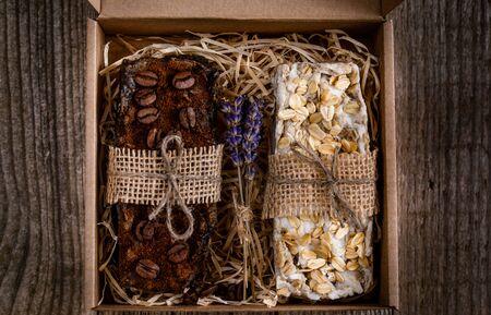 Handmade scrub soap in a cardboard box, decorated with straws, burlap and dry lavender Foto de archivo
