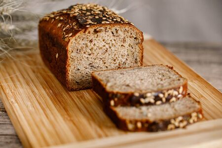 pełnoziarnisty chleb bezglutenowy z dodatkiem siemienia lnianego, słonecznika, nasion chia, sezamu. widok z boku z miejscem na kopię Zdjęcie Seryjne