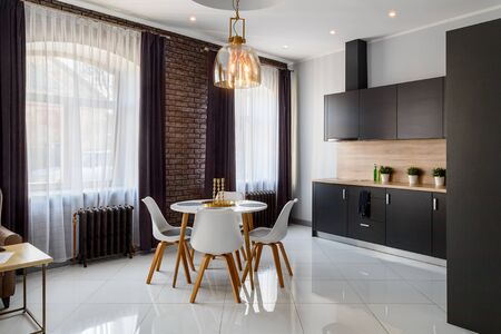 Spacious living room in white-brown tones with white glossy tiles on the floor Foto de archivo