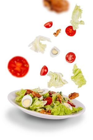 Salad of fresh green leaves, cherry tomatoes, quail eggs, walnuts on a flying saucer with flying ingredients