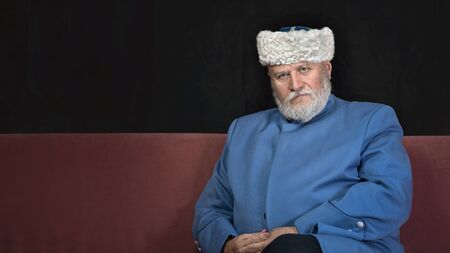 elderly man with a gray beard in a hat and a blue caftan. Cossack costume