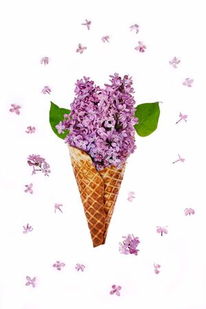 Waffle cone with lilac flower bouquet on white background. Flat lay, top view floral background