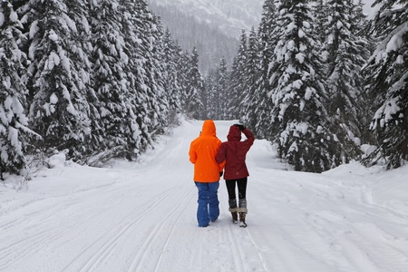 Young couple walking down the road in the mountains near ski resort in Stevens Pass, WA state. USA photo