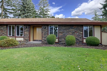 Klein huis met stenen muur Stockfoto