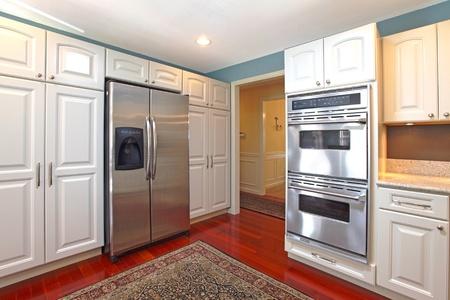 White kitchen with cherry hardwood