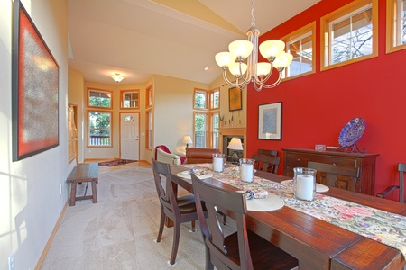 Large red living room with dark brown wood table photo