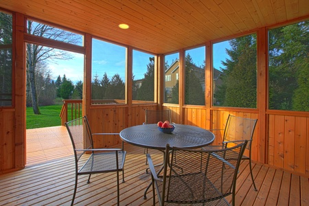 eating area: Covered screen porch with dining table Stock Photo