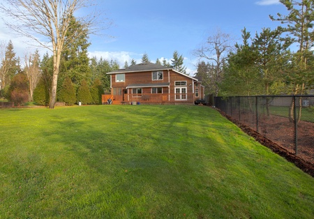 Green grass and large yard with cedar wood house photo