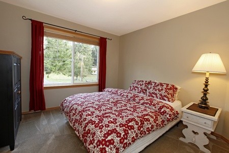 Bedroom with red bed and brown walls photo