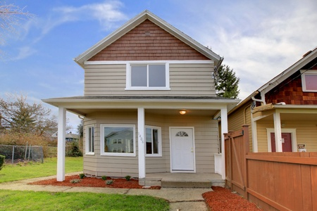 Cute small new beige house with covered front entrance Stock Photo - 12312599
