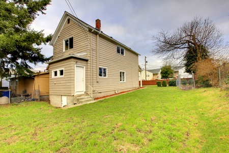 Small beige house with back yard  photo
