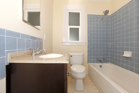 Nice new bathroom with blue tiles and brown cabinet under the sink photo
