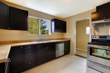 Kitchen black brown cabinets and new appliances Foto de archivo