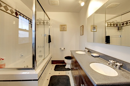 White large bathroom with black rugs and shower photo