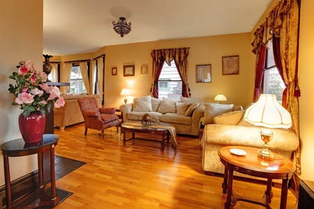 designers interior: Luxury soggiorno con pareti d'oro e tende rosse