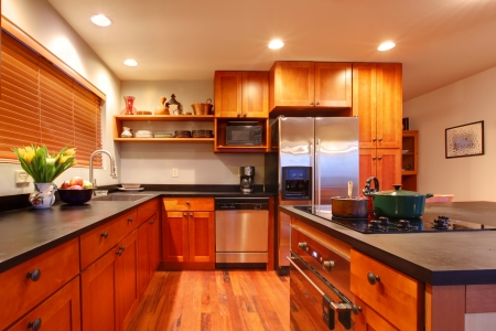 kitchen furniture: Really nice kitchen with cherry wood and hardwood floor Stock Photo