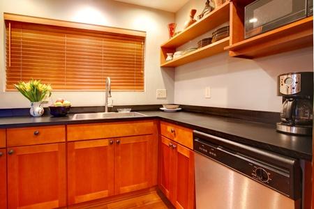 Modern cherry luxury kitchen with black ans stain steal.