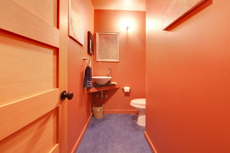 powder room: Modern powder room with red terracotta walls
