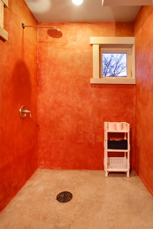 Open large shower with red walls and small window photo
