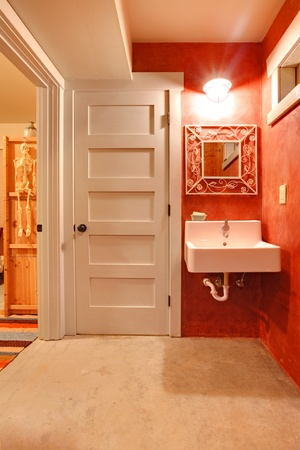 Red walls and large white sink and door near it photo