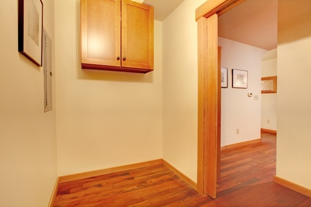 cherry hardwood: Empty laundry room with hallway and cherry hardwood floor