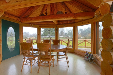 wood molding: Log cabin breakfast area with dining room table and farm view