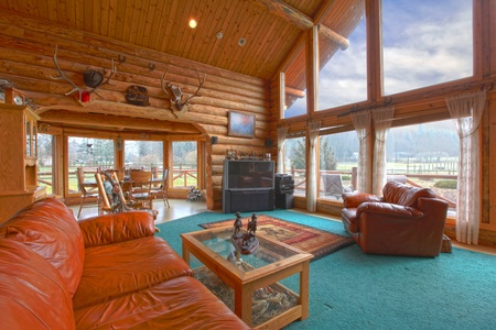country house style: Large living room in the rustic log cabin on the horse farm