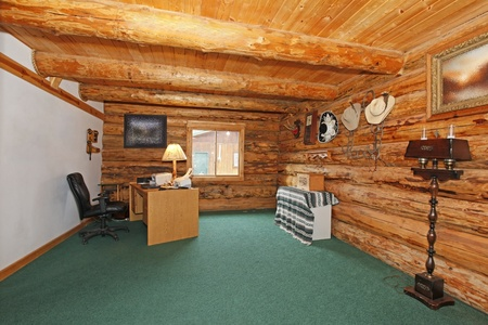 Log cabin office with green carpet and desk photo