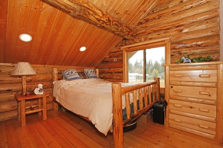 Bedroom in rustic mountain log cabin with large scale furniture Stock Photo - 12312284