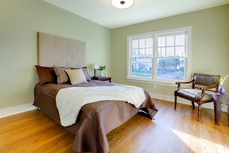 Modern fresh bedroom wtih oak floor and browns bedding Stock Photo