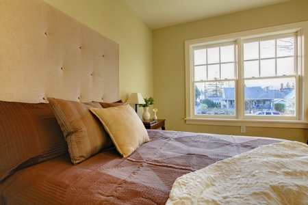 Modern fresh bedroom wtih oak floor and browns bedding Stock Photo - 12312249